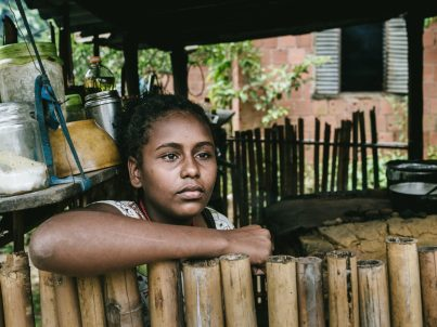 Brazilian girl at her home in the kitchen of a wood stove. Rio de Janeiro State, Brazil.
