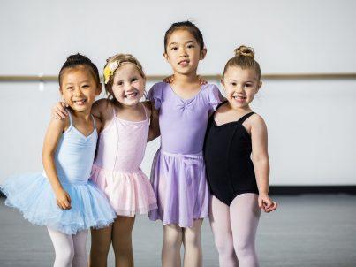 A cute diverse group of little girls at their ballet class
