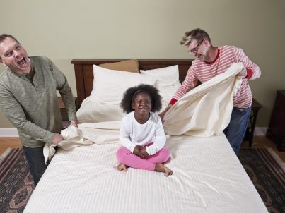 Unconventional family.  Gay couple (30s, 40s) with African American girl (5 years) making the bed.