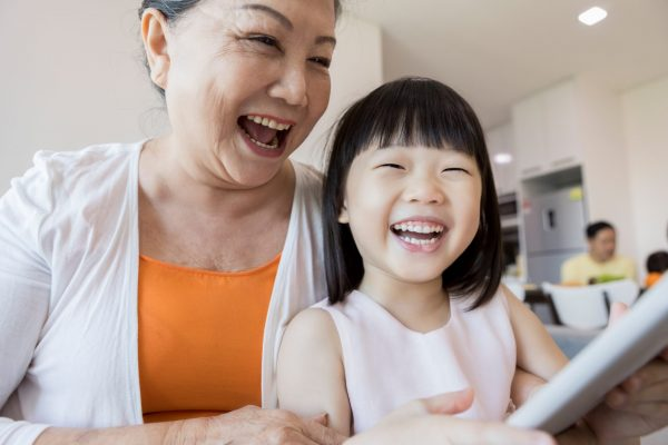 Happy grandmother and her adorable granddaughter watch something on a digital tablet.