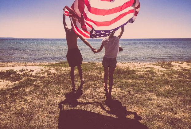 Young couple holding the United States Flag at the beach