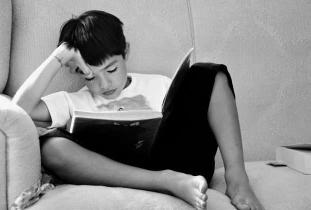 Boy reading on couch